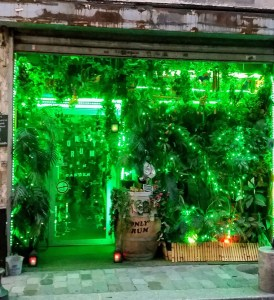 Green lit shop front of a bar called only rum. The entrance and windows are covered in vines and artificial plants.