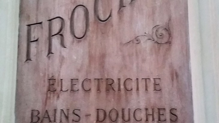 old sign advertising electricity, showers and phones in hotel Frochot