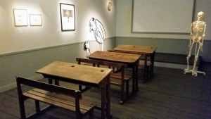 A classroom with 3 desks with benches and scenes of Nicolas and his friends on the wall