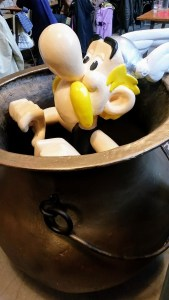 A figurine of Asterix sitting in a large bronze pot labeled as magic potion