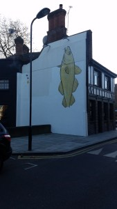 A white wall with a large yellow fish painted on vertically
