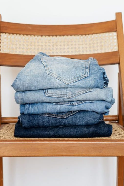 stack of blue jeans on chair