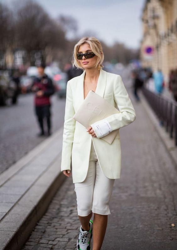Mulher com roupa social branca e óculos de sol de pé na rua