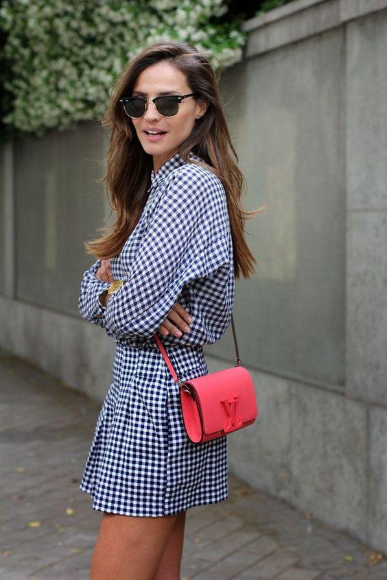 Mulher com vestido estampado e bolsa vermelha