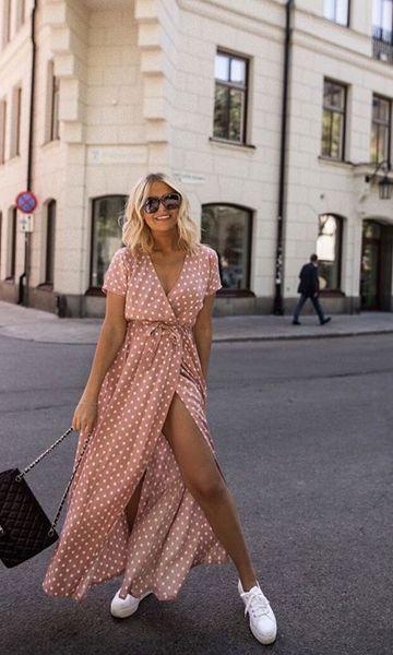 Mulher com vestido mostrando as pernas e óculos de sol