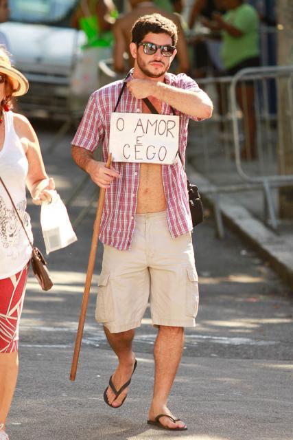 """Homem fantasiado de cego com placa dizendo """"o amor é cego"""""""