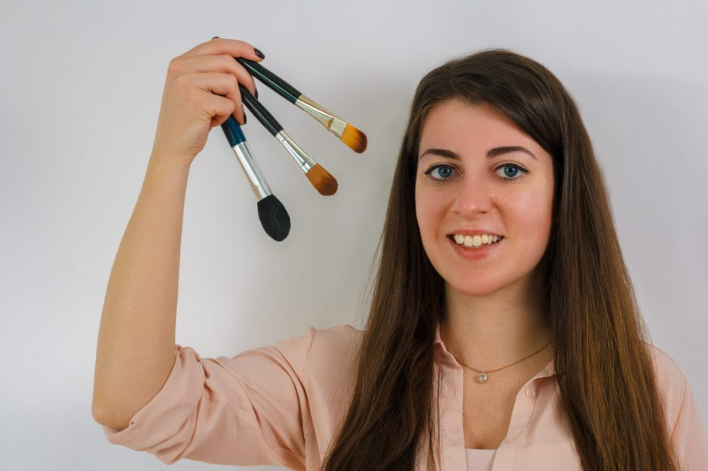 Mulher segurando 3 pincéis de maquiagem próximos ao seu rosto