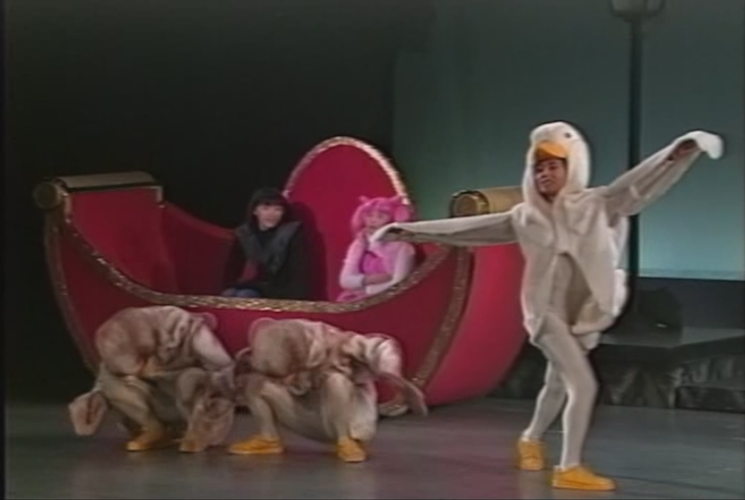Chibiusa and Hotaru sitting in a pink boat while two human-sized ducks sit on the stage/water and one human-sized goose is posing.