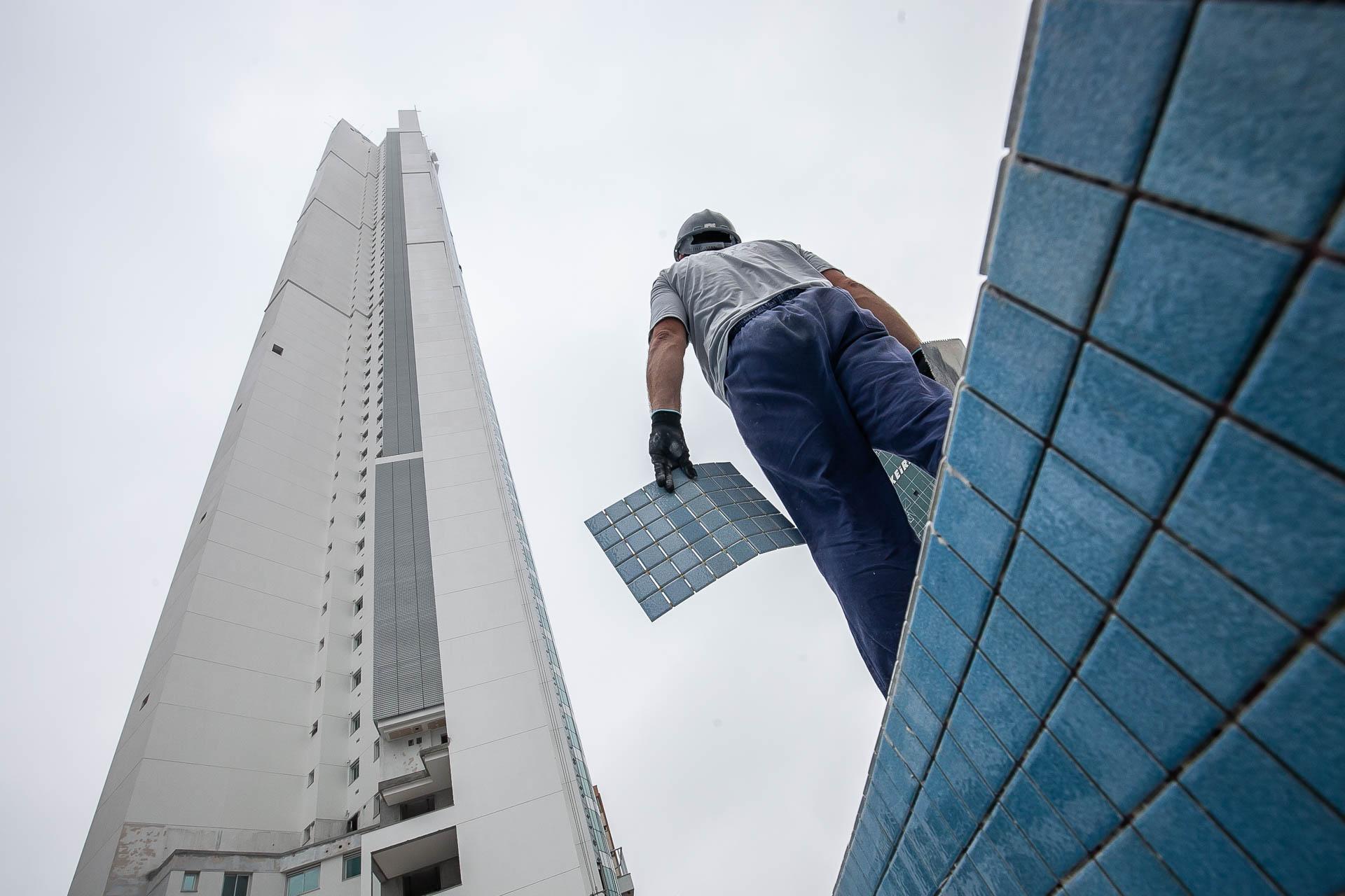 Trabalhador da construção civil observa o topo do Infinity Coast, da FG, um dos prédios mais altos do Brasil
