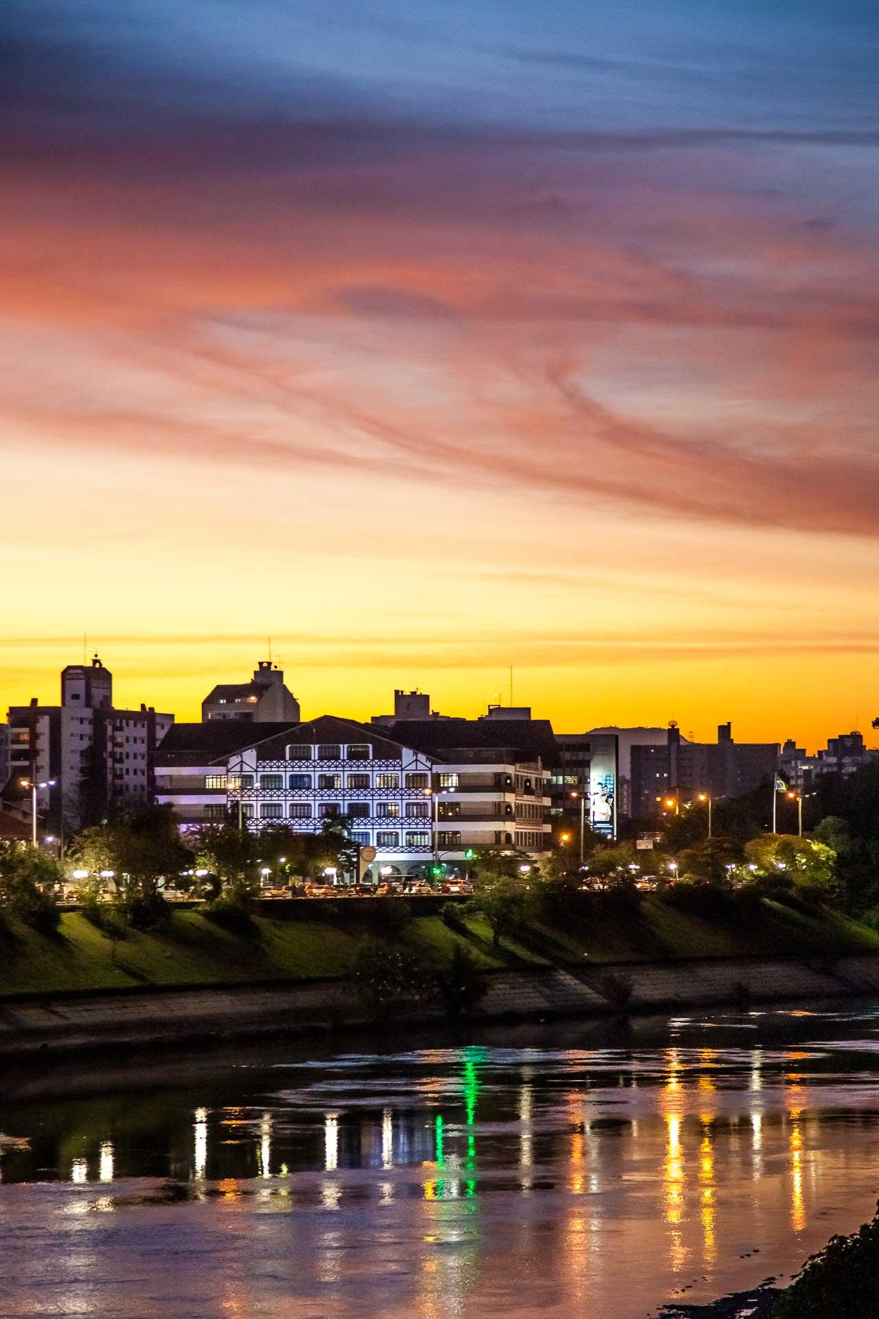 Um crepúsculo multi colorido no Centro de Blumenau, com destaque para a prefeitura e o Rio Itajaí-Açu