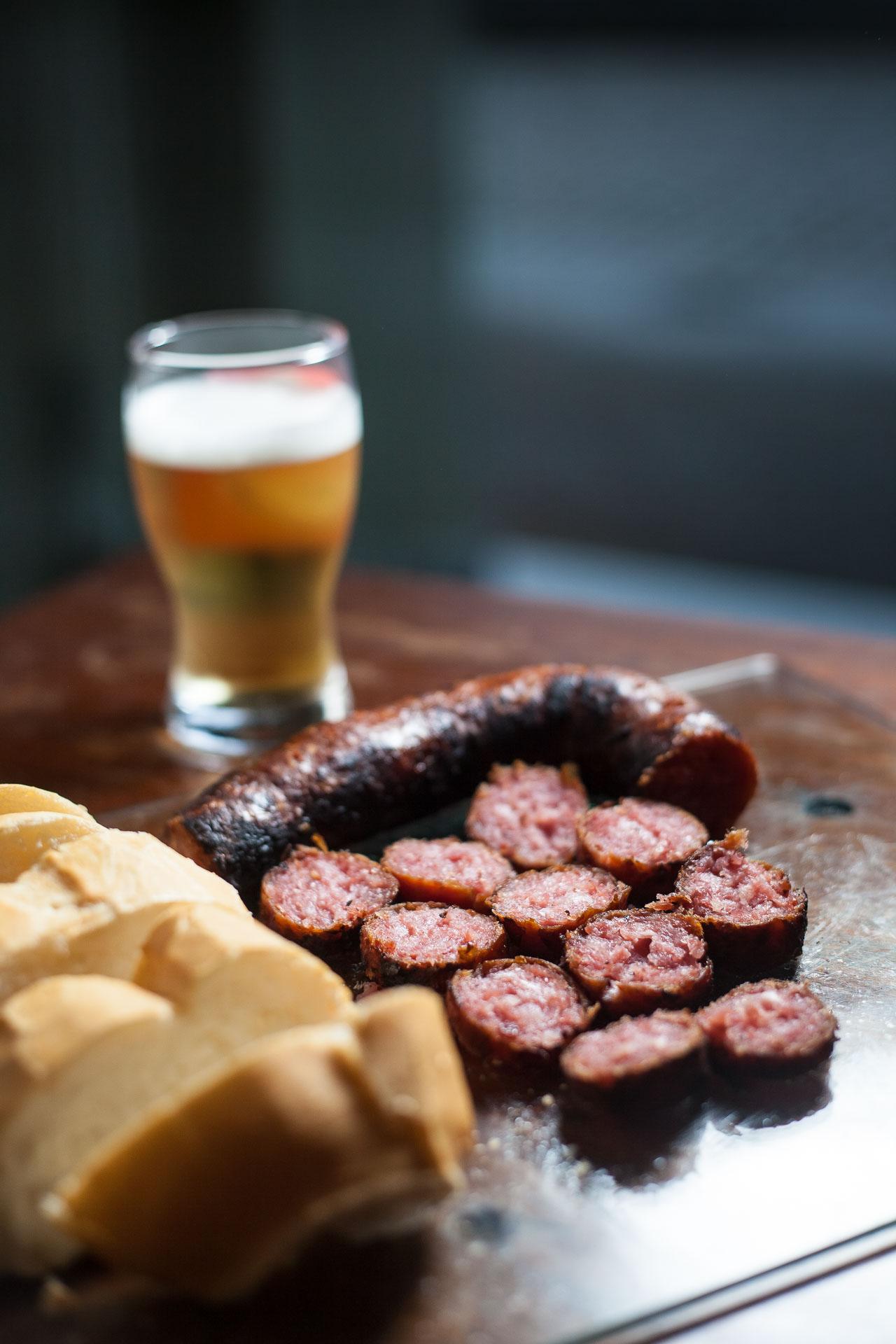 Linguiça Blumenau frita na panela de barro, com pão e cerveja para acompanhar