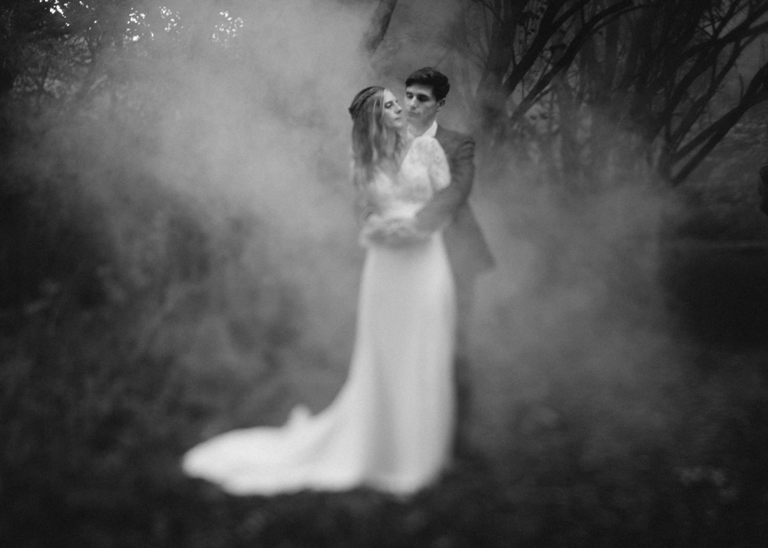 Married couple cuddling in a forest surrounded by smoke