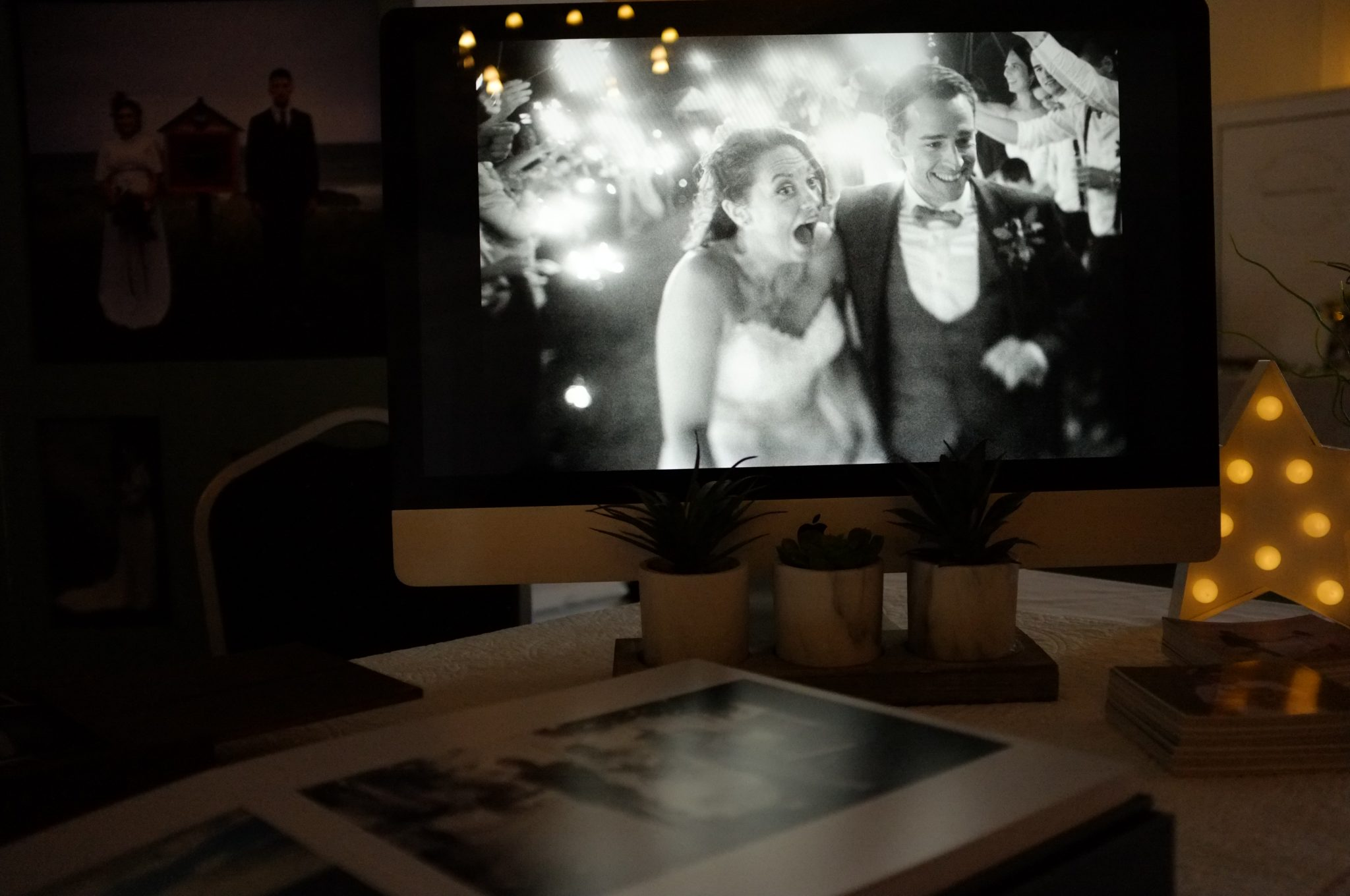 iMac screen on wedding fair stand with a picture of a surprised bride and groom