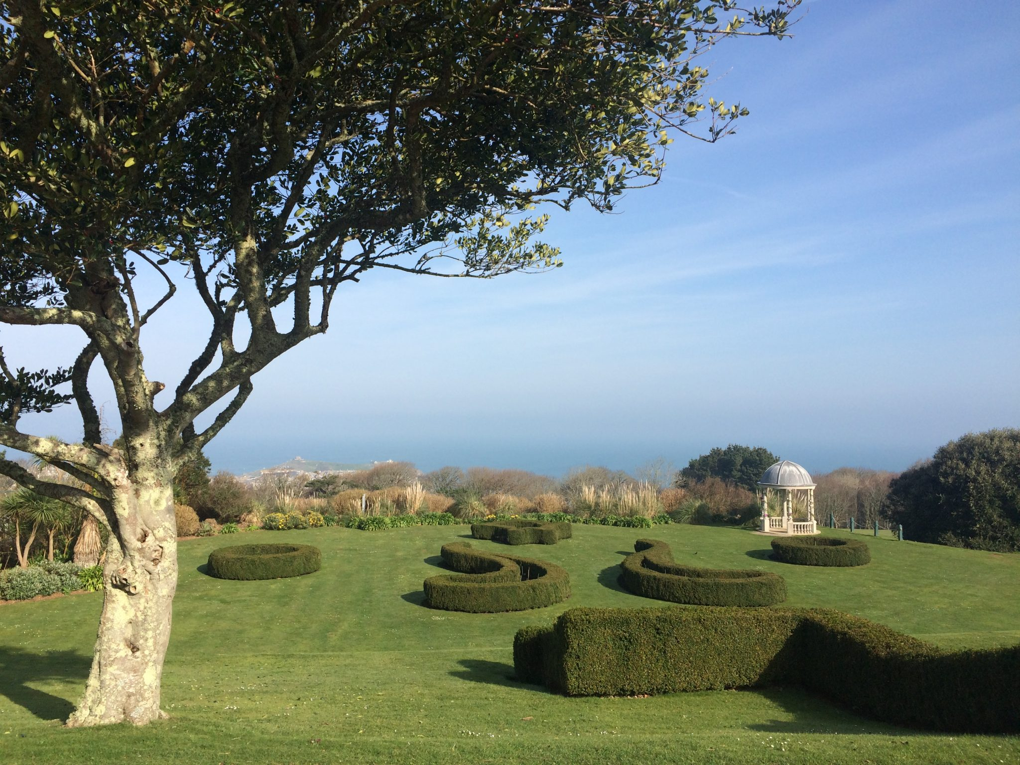 Tregnna castle gardens with a blure sky and lush green hedges and grass