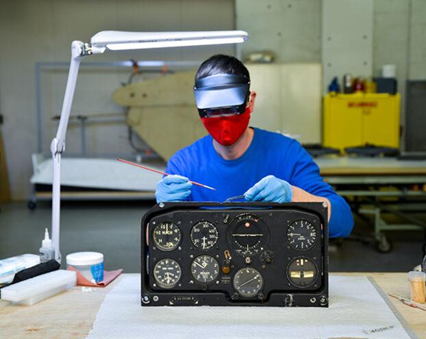 Patrick Dettling, spécialiste de la restauration du patrimoine technique, utilise une brosse pour nettoyer le tableau de bord d'un avion de 1962.