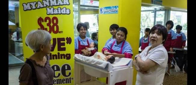 A Singapour, des employées domestiques changent des couches sur des poupées pour montrer leur efficacité.