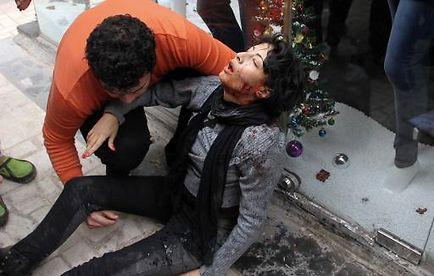 Une personne porte assistence le 24 janvier au Caire, après des affontements entre manifestants de gauche et la police, à Shaïma al-Sabbagh, qui décedera plus tard.