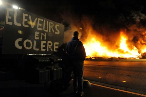 Un homme regarde des pneus en train de brûler lors d'une opération d'agriculteurs en colère, le 2 juillet 2015 à Saint-Brieuc