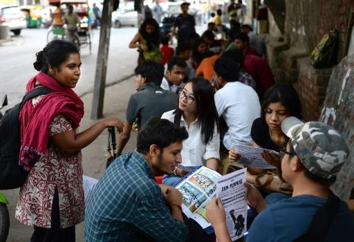 Une étudiante indienne distribue des tracts devant l'université de New Deli contre les mesures discriminatoires dont notamment le couvre-feu qui leur est imposé, le 30 septembre 2015