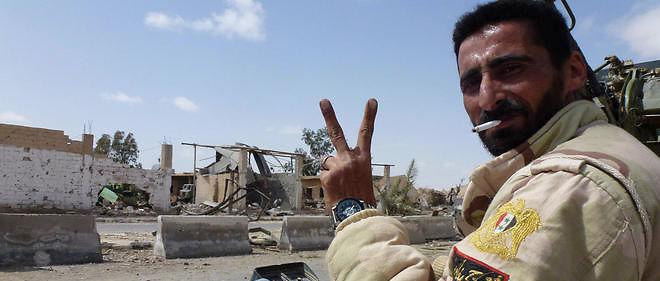 Un soldat prorégime fait le V de la victoire dans la ville moderne de Palmyre.