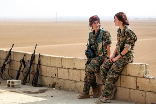 Chirine (G) et Kazîwar (D), membres des Unités de protection de la femme kurde (YPJ) discutent sur le toit d'une maison du village syrien de Mazraat Khaled, à environ 40 km de de Raqa, le 9 novembre 2016 © delil souleiman AFP