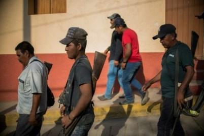 Des civils armés marchent dans les rues de Tlacotepec, municipalité d'Heliodoro Castillo au Mexique, le 24 mars 2018 © Pedro PARDO AFP