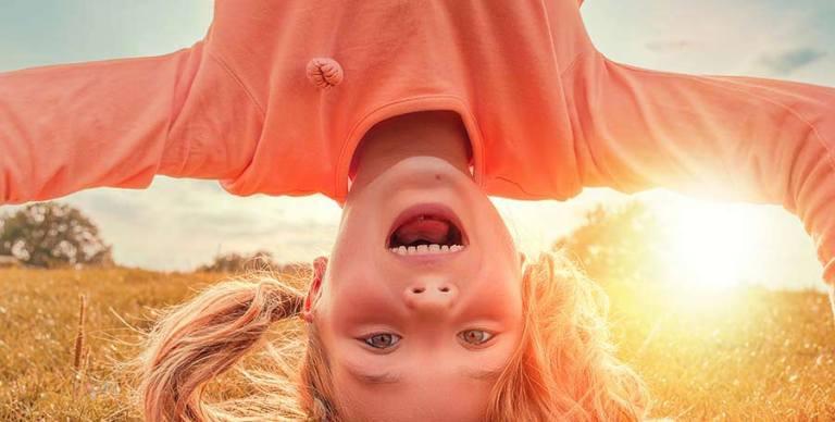Mädchen steht Kopf und hat Spaß dabei