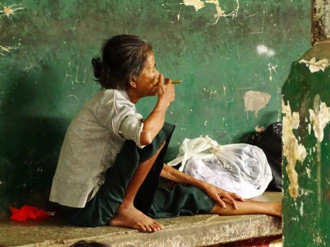 Une vieille femme fumant le cigare sur le quai du circular train à Yangon
