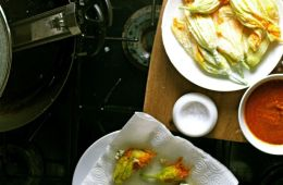 at the stove with fried zuchini blossoms, salt and sauce