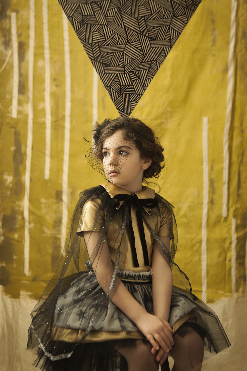 girl sat in gold dress by yellow backdrop