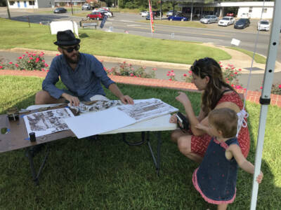 After the majority of the on-site work is blocked in, Les heads under the shade of the market canopy to meet new art lovers.