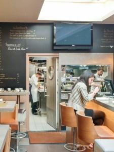 Salle du restaurant les Cocottes de Christian Constant vue sur les cuisines