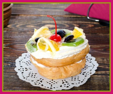 Choux pastry with fruit on a wooden background. Rustic style.