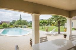 Maison périgourdine vue d'extérieur via la terrasse couverte montrant ainsi le coin jardin et son aménagement.