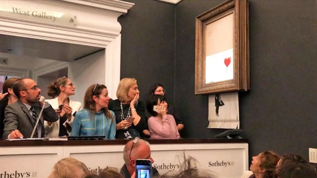 """L'opera di Banksy """"ragazza col palloncino"""" si autodistrugge durante un'asta di Sotheby's a Londra, i presenti la guardano stupiti."""