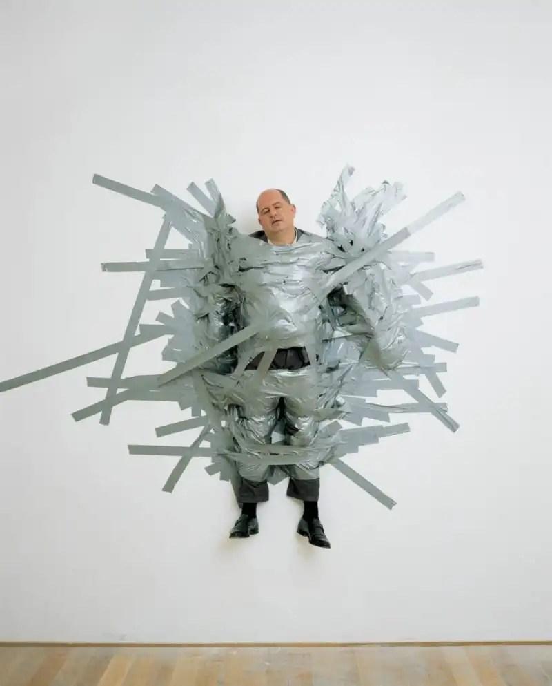 il gallerista d'arte Massimo De Carlo viene appeso al muro con dello scotch nella sua galleria di Milano dall'artista Maurizio Cattelan