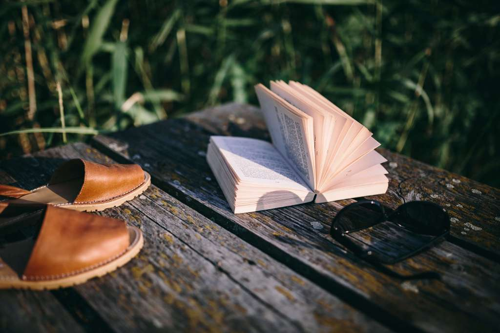 book and shoes on dock