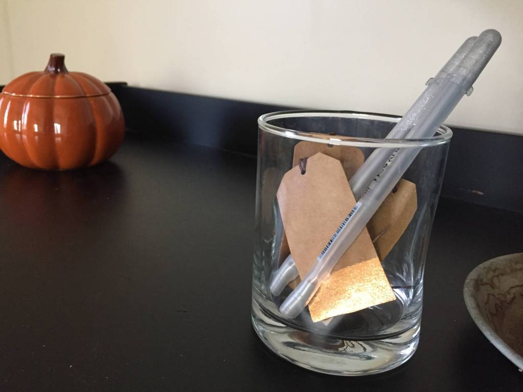 paper craft tags and silver pens in cup