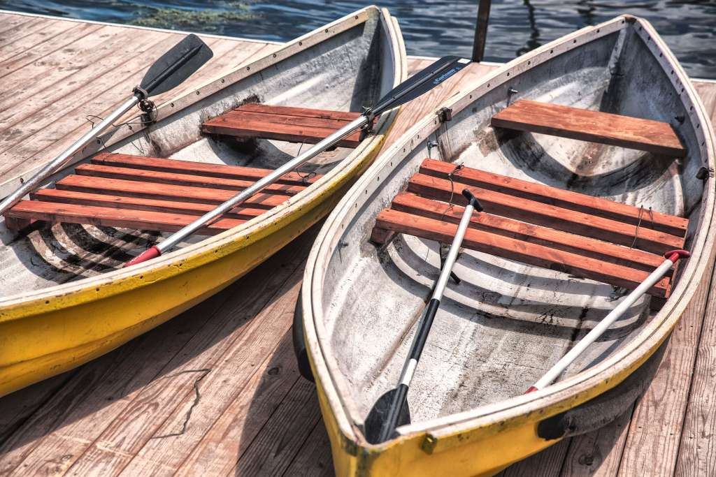 Two empty canoes sitting side by side on a dock