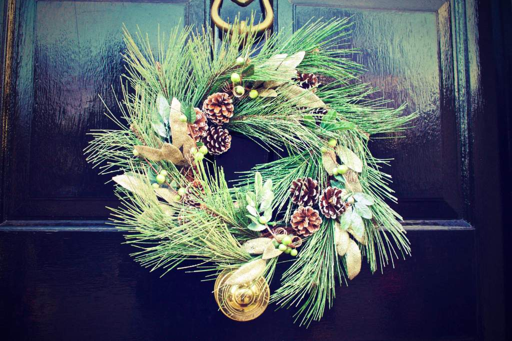 Christmas wreath on black door with ornaments
