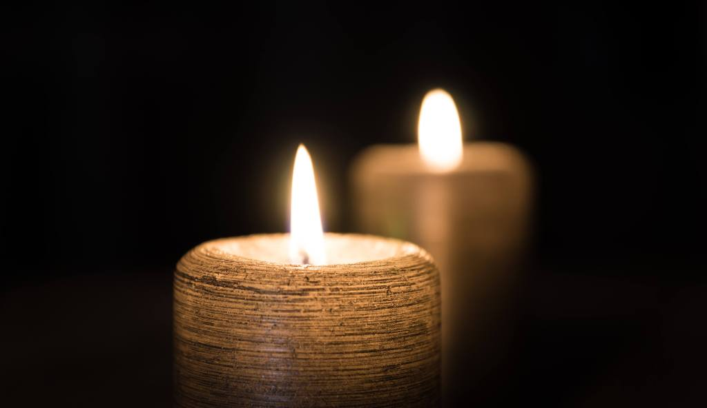 Single Candle in total darkness with reflection