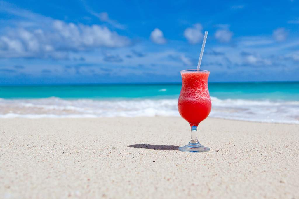 Spring Break With Kids Prep Guide - cocktail sitting on beach image