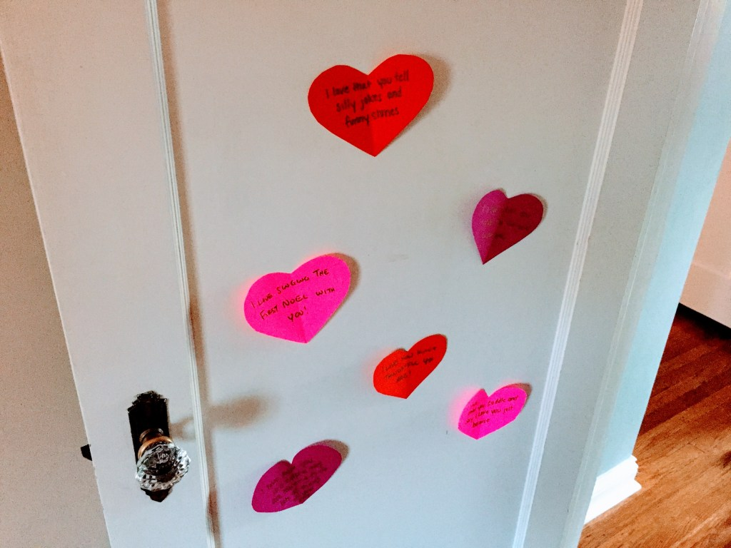 Simple Valentine's Day Traditions for Families - paper hearts with notes on kids door