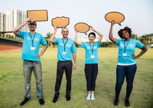 """Four young adults in blue t-shirts reading """"VOLUNTEER"""" smiling and holding cardboard cut-outs of speech bubbles over their heads."""