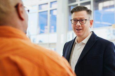 A stock photo of two men in business having a conversation, illustrating the power of a personal connection instead of a cold letter of interest.