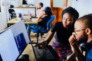 A photo of two tech professionals looking at a software program on a computer in front of them and thinking, illustrating the strategy of focusing on collaboration when answering tough interview questions about a conflict you encountered. Photo by NESA by Makers on Unsplash