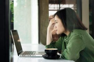 A photo of a woman looking at a laptop intently with a cup of coffee in front of her, illustrating the in-depth research needed to make a pain letter work.
