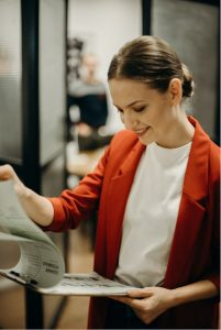 A stock photo of a woman smiling looking at resumes on a clipboard, used to illustrate what hiring managers look for when reading a resume.