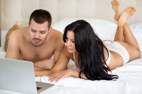 Young couple lying on bed with laptop