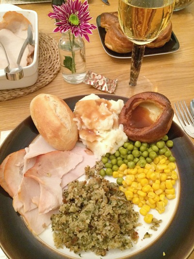 A plate filled with turkey, mashed potatoes, stuffing, gravy, peas and sweetcorn for Thanksgiving